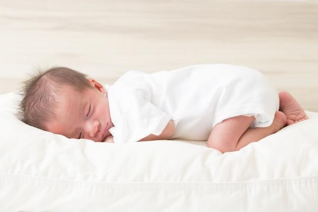 Śpiąca nowonarodzona chłopiec na łóżku, 14 dni życia, sen dzieciaka pojęcie