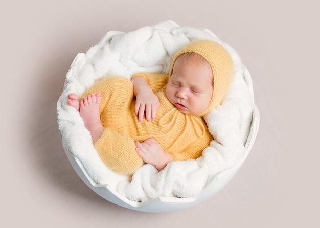 Śpiąca noworodek zwinięty w kłębek na okrągłym koszu