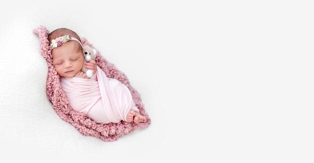 Śpiąca noworodka dziewczynka owinięta różowym kocykiem