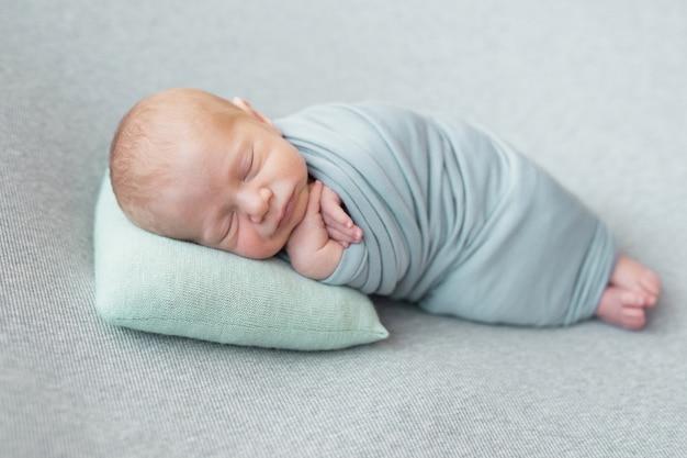 Śpiąca noworodka. zdrowa i medyczna koncepcja. zdrowe dziecko, koncepcja szpitala i szczęśliwe macierzyństwo. niemowlę szczęśliwa ciąża i poród. motyw dziecięcy. artykuły dla niemowląt i dzieci