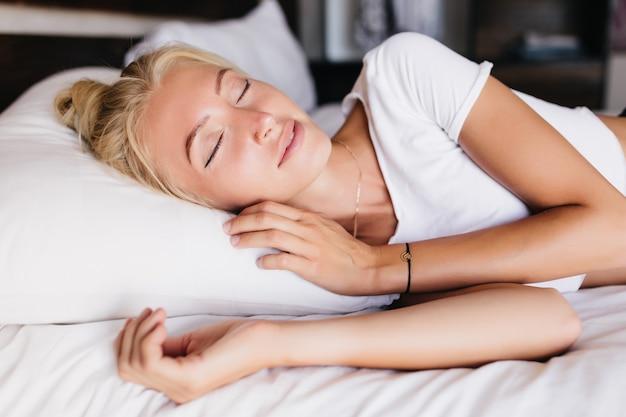 Śpiąca opalona kobieta leżąca na poduszce. blondynka kaukaski odpoczywa w łóżku.