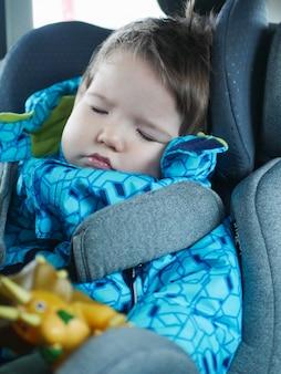 Śpiące dziecko jeździ na foteliku samochodowym. szczęśliwa dziecko przejażdżka samochodem. bezpieczeństwo dziecka. ładny chłopak śpi w samochodzie w foteliku dziecięcym