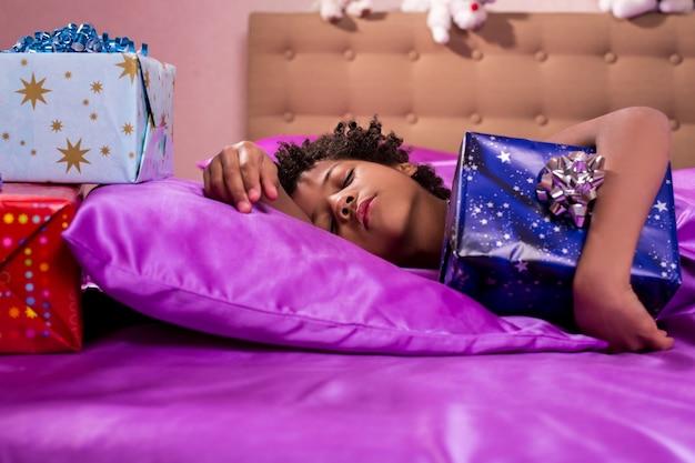 Śpiące dziecko przytula pudełko upominkowe. śpiący chłopiec afro przytula obecny. wyobraź sobie jego radość. dzisiejszy poranek będzie cudowny.