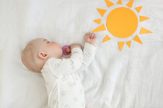 Śpiące dziecko w łóżku rano. czas wstawać. poranne słońce niemowlę śpiący. małe dziecko śpi.