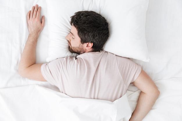 Śpiącego młodego człowieka rano pod kocem w łóżku leży
