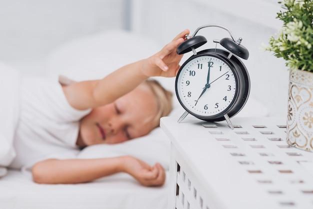 Śpiący chłopak zatrzymujący alarm