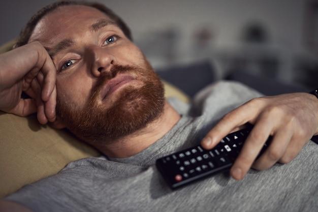 Śpiący człowiek ogląda telewizję na kanapie