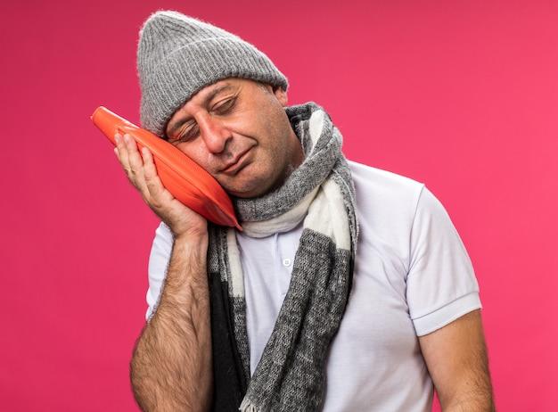 Śpiący dorosły chory kaukaski mężczyzna z szalikiem na szyi w czapce zimowej trzymającej i kładącej głowę na termofor izolowanej na różowej ścianie z kopią przestrzeni