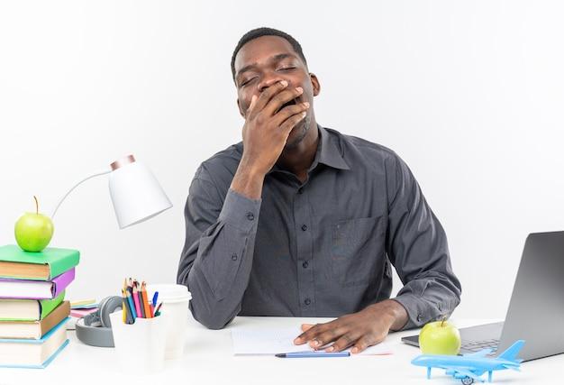 Śpiący młody afroamerykański uczeń siedzący przy biurku ze szkolnymi narzędziami ziewający i kładący rękę na ustach