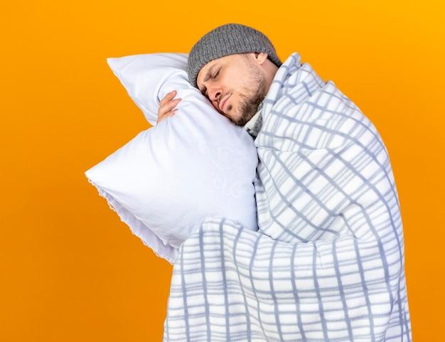 Śpiący młody blondyn chory w czapce zimowej i szaliku owiniętym w kratę trzyma i kładzie głowę na poduszce odizolowanej na pomarańczowej ścianie