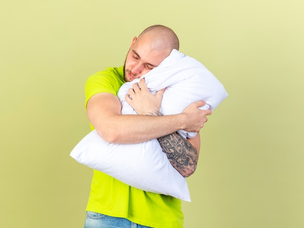 Śpiący młody chory przytula się i kładzie głowę na poduszce odizolowanej na oliwkowej ścianie