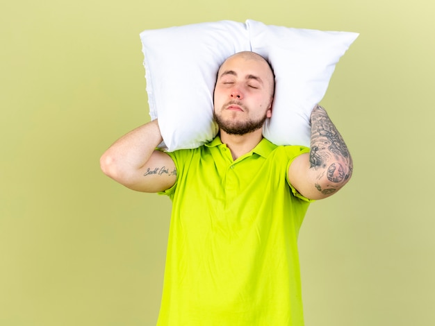 Śpiący młody chory trzyma poduszkę za szyją na białym tle na oliwkowej ścianie