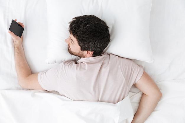 Śpiący młody człowiek rano pod kocem w łóżku leży przy użyciu telefonu komórkowego
