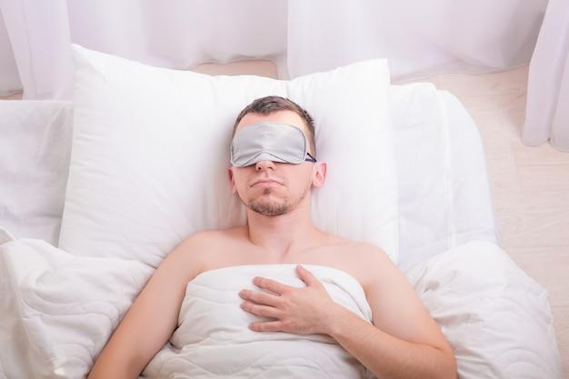 Śpiący młody człowiek w masce snu na łóżku.
