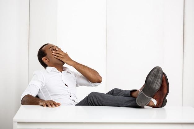 Śpiący młody pomyślny biznesmen ziewa, siedzący przy miejscem pracy
