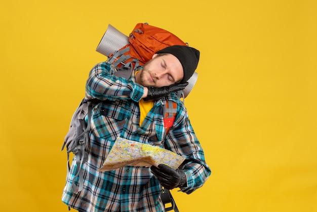 Śpiący młody turysta w czarnym kapeluszu trzymający mapę