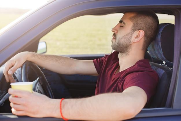 Śpiący nieogolony młody mężczyzna siedzi w samochodzie