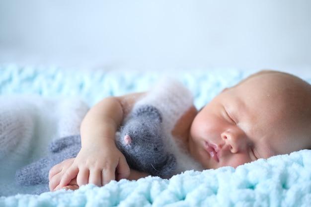Śpiący noworodek leży na niebieskim kocu, a w rączkach dziecka szydełkowana zabawkowa mysz