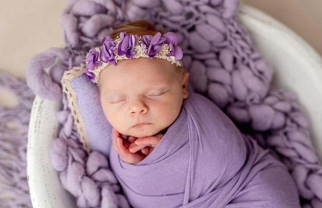 Śpiący noworodek zawinięty w fioletowy kocyk