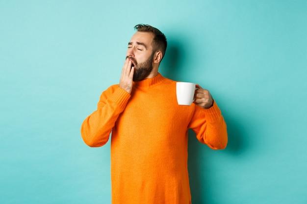Śpiący przystojny mężczyzna pije kawę i ziewając, stoi w pomarańczowym swetrze na tle jasnoniebieskiej ściany