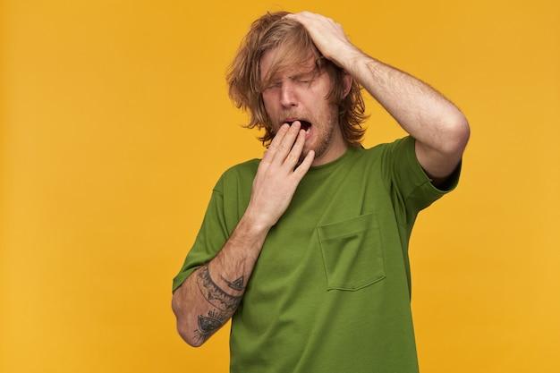 Śpiący, zmęczony facet z rozczochranymi blond włosami, brodą i wąsami. na sobie zieloną koszulkę. ma tatuaże. podrap się po głowie. ziewa zakrywając usta. stań odizolowany na żółtej ścianie