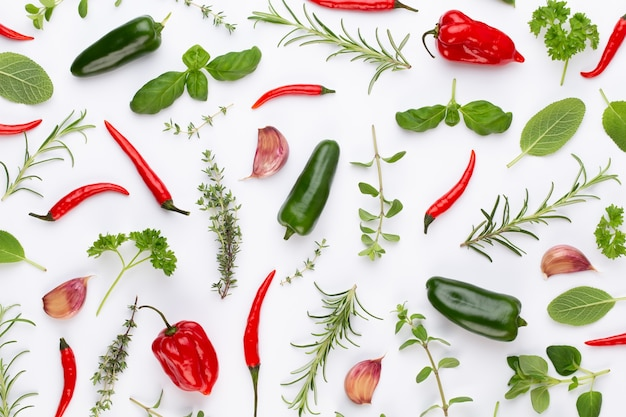 Spice ziołowe liście i papryczka chili na białej powierzchni. wzór warzyw. kwiaty i warzywa na białej powierzchni. widok z góry, płaski układ.
