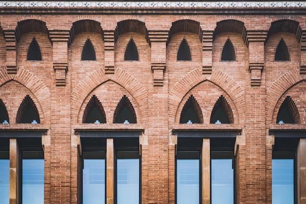 Spiczaste łukowe okna pawilonu starego kompleksu la maternitat zbudowanego w stylu modernistycznym