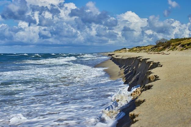 Spienione fale morskie i piękne zachmurzone niebo nad piaszczystą plażą z wydmami