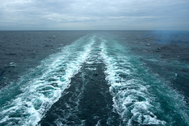 Spienione fale na powierzchni wody za statkiem wycieczkowym