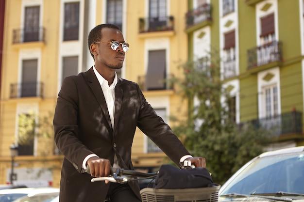 Spieszę do biura. biznesmeni, ekologia, transport i koncepcja miejskiego stylu życia. pewny siebie, przyjazny dla środowiska, afrykański amerykański przedsiębiorca w formalnych strojach i okularach przeciwsłonecznych na rowerze do domu z pracy na rowerze