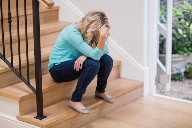 Spięta kobieta siedzi na schodach z ręką na czole