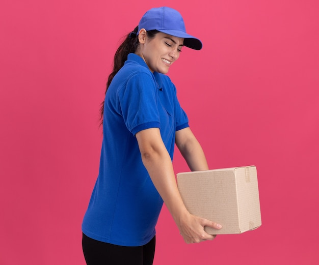 Spięta młoda dostawa dziewczyna ubrana w mundur z czapką trzymającą pudełko na różowej ścianie