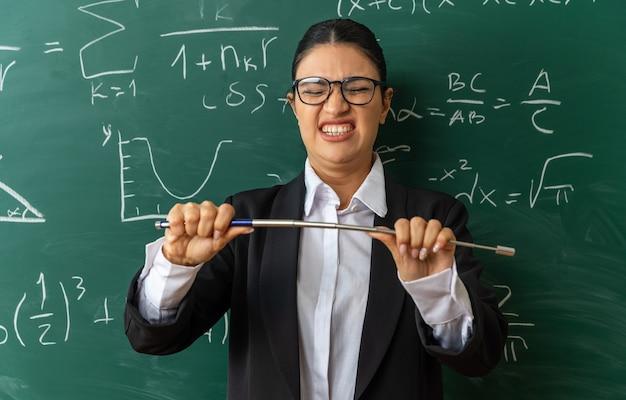 Spięta młoda nauczycielka w okularach, stojąca przed tablicą, trzymająca kij w klasie