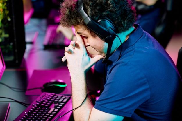Spięty lub zmartwiony młody mężczyzna w słuchawkach dotyka twarzy, lekko pochylając się nad klawiaturą przed monitorem komputera