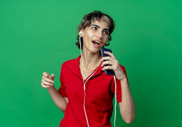 Śpiewa młoda kaukaska dziewczyna z fryzurą pixie, noszącą słuchawki i używającą telefonu komórkowego jako mikrofonu, patrząc z boku