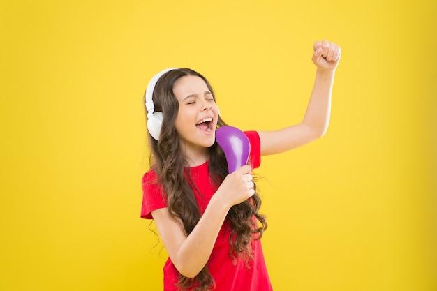 Śpiewaj teksty. dziecko nastolatki cieszyć się muzyką w słuchawkach. mała dziewczynka korzystających z ulubionej muzyki. złap rytm. dziecko słuchania muzyki słuchawki. rozrywka i zabawa. cały muzyczny świat w jej uszach.