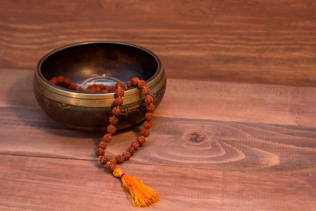 Śpiewająca miska i rudraksha na drewnie