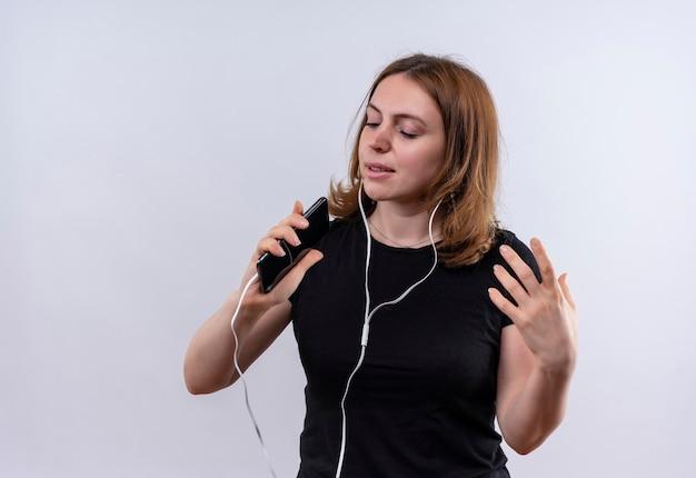 Śpiewająca młoda kobieta dorywczo nosząca słuchawki i używając telefonu komórkowego jako mikrofonu na odosobnionej białej przestrzeni z miejsca na kopię