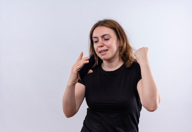 Śpiewająca młoda kobieta dorywczo za pomocą telefonu komórkowego jako mikrofonu na odosobnionej białej przestrzeni z miejsca na kopię