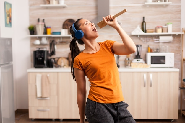 Śpiewanie na drewnianej łyżce w słuchawkach w kuchni