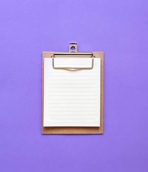 Spinacz do papieru na fioletowym, płaskim ułożeniu