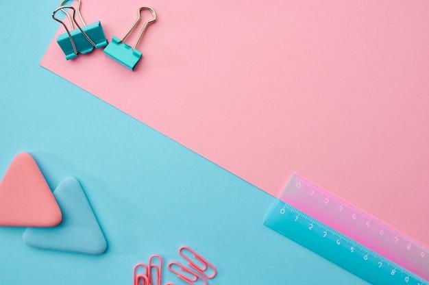 Spinacze i linijka zbliżenie, niebieskie i różowe tło. artykuły biurowe, akcesoria szkolne lub edukacyjne, narzędzia do pisania i rysowania