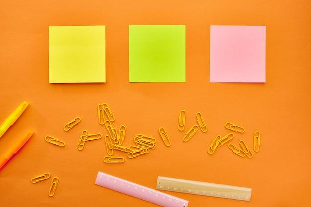 Spinacze, notatnik i linijka zbliżenie na pomarańczowym tle. artykuły biurowe, akcesoria szkolne lub edukacyjne, narzędzia do pisania i rysowania