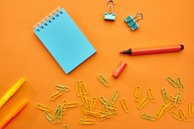 Spinacze, notatnik i marker zbliżenie na pomarańczowym tle. artykuły biurowe, akcesoria szkolne lub edukacyjne, narzędzia do pisania i rysowania