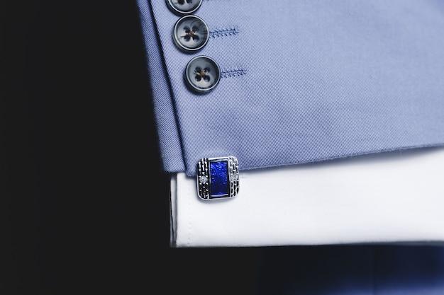 Spinki do mankietów na rękawie niebieskiego garnituru z bliska