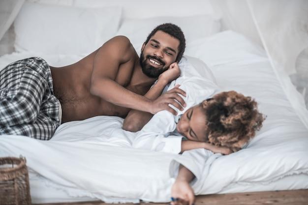 Śpioch. uśmiechnięty młody brodaty afroamerykanin i zdrowo śpiąca żona w białej koszuli leżąc na łóżku w domu