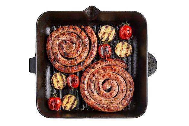 Spiralne kiełbaski pomidory i cukinia na patelni grillowej na białym talerzu