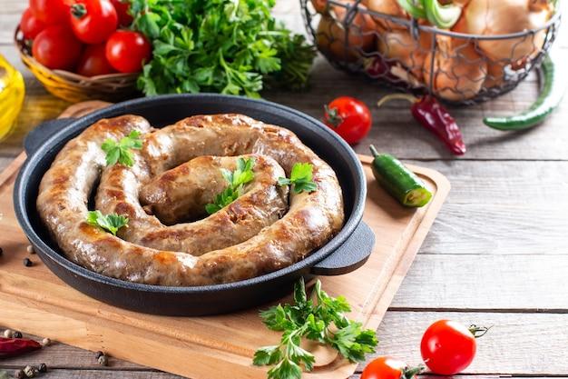 Spiralne pyszne kiełbaski z grilla na patelni z warzywami na drewnianym stole, miejsce