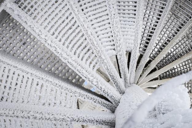 Spiralne schody są pokryte śniegiem. niebezpieczne zejście