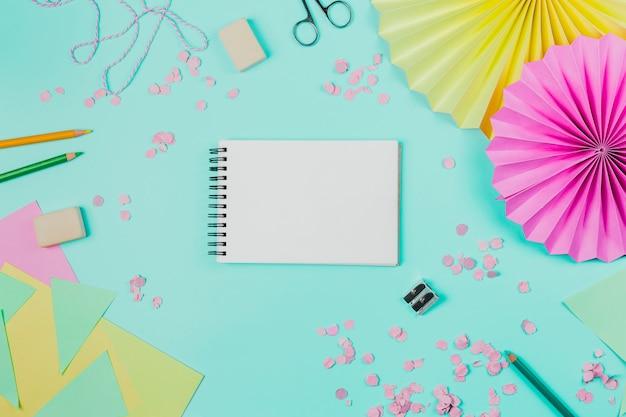 Spiralny czarny notatnik otoczony konfetti; gumka do mazania; kolorowe kredki i papier